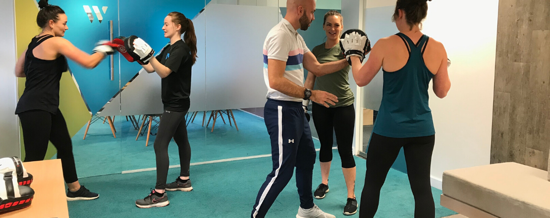 Man teaching women in a workplace to do boxercise